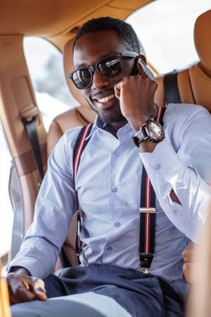 blackman: Black man in sunglasses with smartphone in the car.