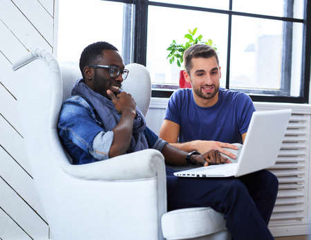 Blackman and white guy warking with laptop.