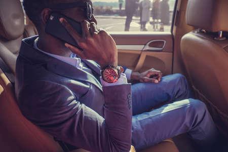 Black man in the car talking on smartphone.