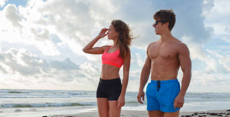 sport clothes: Summer time. Fitness couple on the beach. Stock Photo