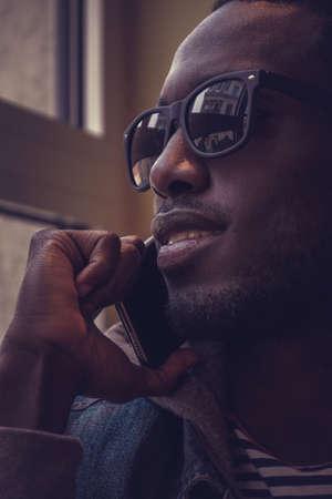 blackman: Blackman in sunglasses talking on smartphone.