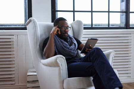 blackman: African american man sitting on chair and working with laptop.