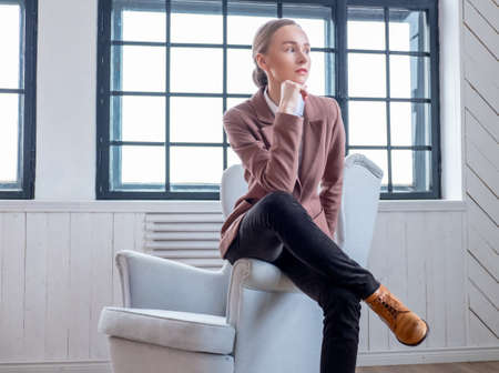 sits on a chair: Toughtful woman sits on a chair. Stock Photo