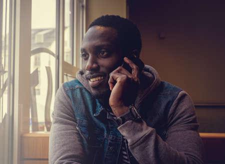 blackman: Positive african american man talking on smartphone. Stock Photo