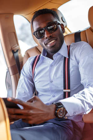 Black man in sunglasses with smartphone in the car.