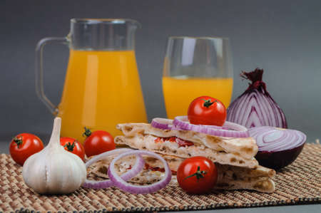 garlic bread: Glass with orange juice, red tomatoes and piece of garlic on the table.