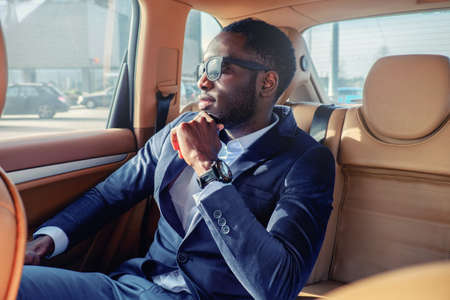 Blackman in a suit in the car.