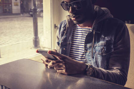blackman: Blackman in sunglasses using smartphone. Stock Photo