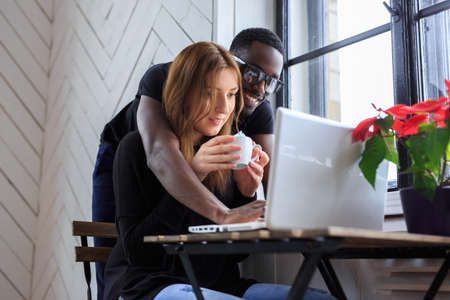blackman: Blackman and young woman working with laptop.