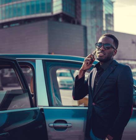 blackman: Black man in sunglasses talking by smartphone near the car.