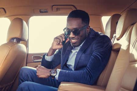 blackman: Black man in the car talking on smartphone.
