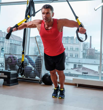 middle age man: Middle age man training with gymnastic rings in a gym club.