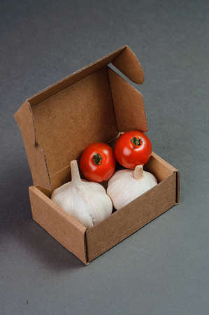 garlics: Red tomatoes and garlics in the box. Stock Photo