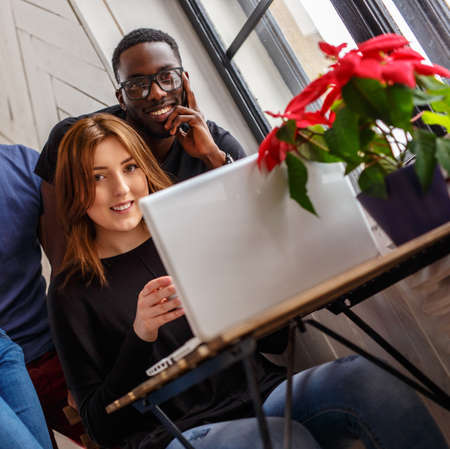 Smiling black man and a woman with laptop.
