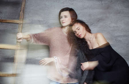 pullovers: Two brunette women in stylish pullovers. Stock Photo