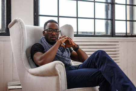 A black man relaxing  in a white chair. Stock Photo