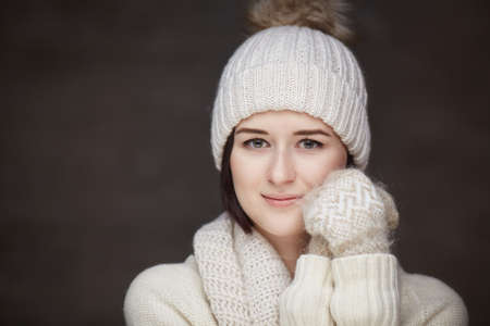 Portrait of a girl in a white sweater and winter hat.