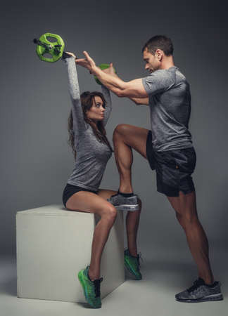 workouts: Muscular man helping a woman with workouts. Stock Photo