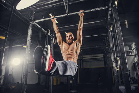 nude stomach: Shirtless bearded man doing stomach exercises on a horizontal bar.