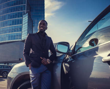 blackman: Casual black man in sunglasses posing near a car in a city center. Stock Photo