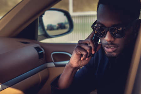 Black man in sunglasses talking by smartphone in the car. Stock Photo