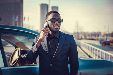 blackman: Black man talking by smartphone near the car.