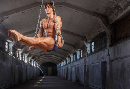 workouts: Man workouts in the air with gimnastic rings.