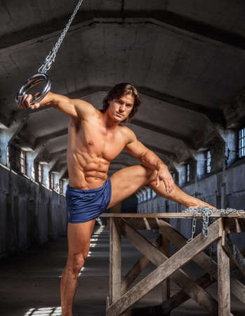 suntanned: Flexible suntanned man doing tricks with gymnastic rings in a tunnel.