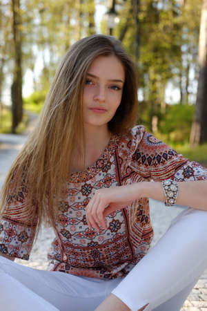 white pants: Cute long hair female in white pants sitting on the road in a summer park.