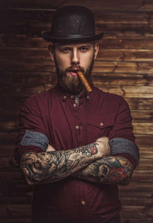 Bearded man with tattooes on arms smoking cigar. Stockfoto