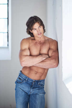 sex symbol: Muscular suntanned guy in denim jeans with crossed arms  posing in natural light.