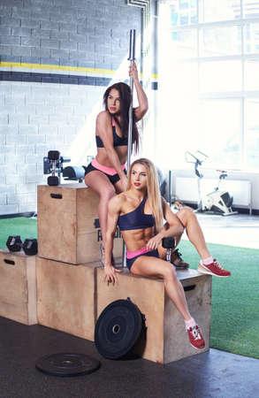 medalist: Sexy blond and brunette females in underwear posing on winner podium in gym club.