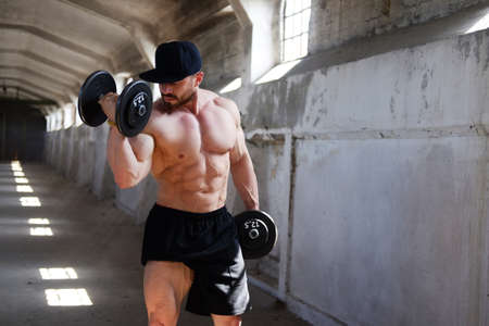suntanned: Awesome male bodybuilder in black cap and shorts exercising with dumbbells in a warehouse.