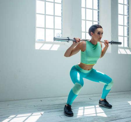 cuclillas: Una mujer en ropa deportiva azul en cuclillas con la barra sobre los hombros.