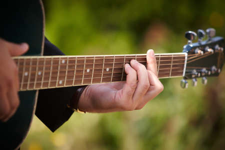 A man playing chords on guitar. Stock Photo