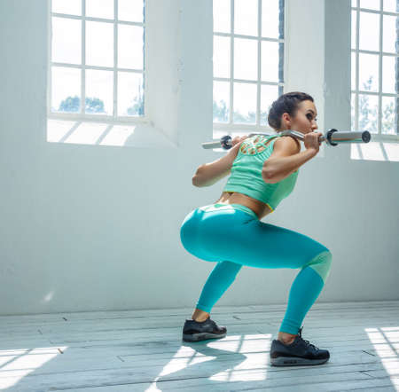 Fitness woman from the back in azure sportswear doing squats with barbell on her shoulders.