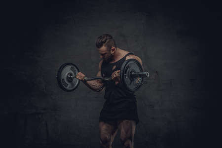 workouts: Bodybuilder doing biceps workouts on grey background in studio. Stock Photo