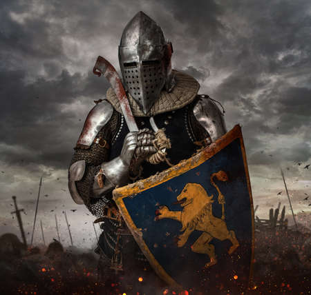 battlefield: Knight with sword in battlefield with dark clouds on background. Stock Photo