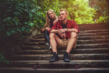 moder: Casual moder young skateboarders couple posing on footway in a forest park.