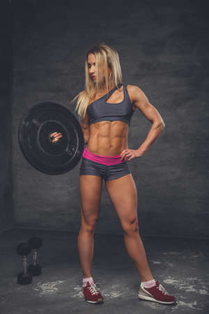 Blond female fitness model holding barbell weight on a grey background in a studio.