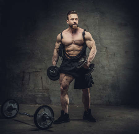 Full body portrait of bodybuilder with dumbbells in a studio on dark grey background.