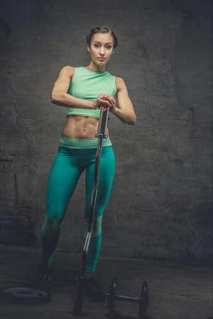 hottie: Full body picture of sporty female in azure sportswear holding barbell.