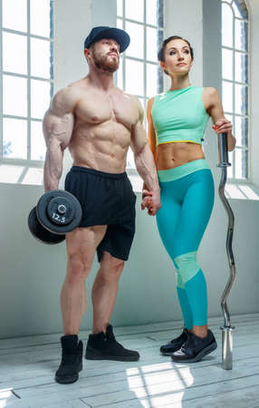 muscular body: Sporty couple posing in natural light from window.