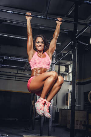 stabilization: Athletic brunette female in pink sportswear doing abs exercises on horizontal bar. Stock Photo