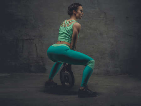 squats: Athletic female in a zure sportswear doing squats.