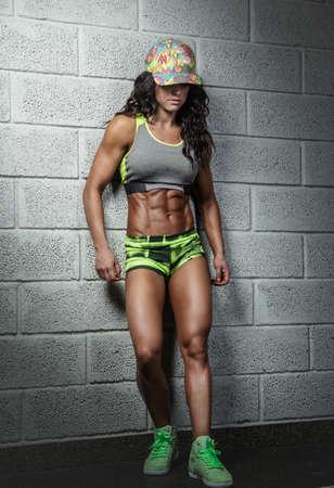 Suntanned abdominal female fitness model posing over grey bricks wall. Stock Photo