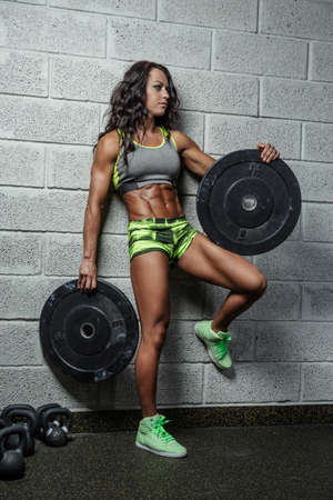suntanned: Athletic suntanned female fitness model holding barbell weight over wall from grey bricks. Stock Photo