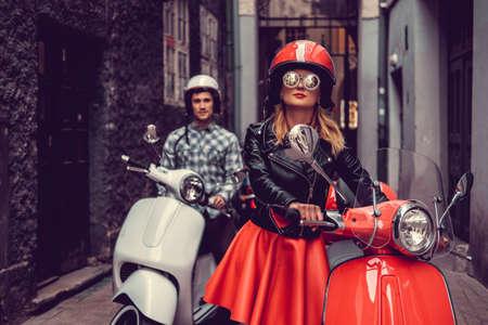 Mannelijke en vrouwelijke op scooters in een stad. Stockfoto