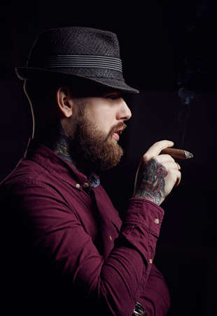 smoking a cigar: Bearded man in a hat smoking a cigar.