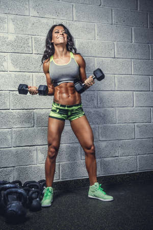suntanned: Sporty suntanned female posing with dumbbells over grey brick wall. Stock Photo